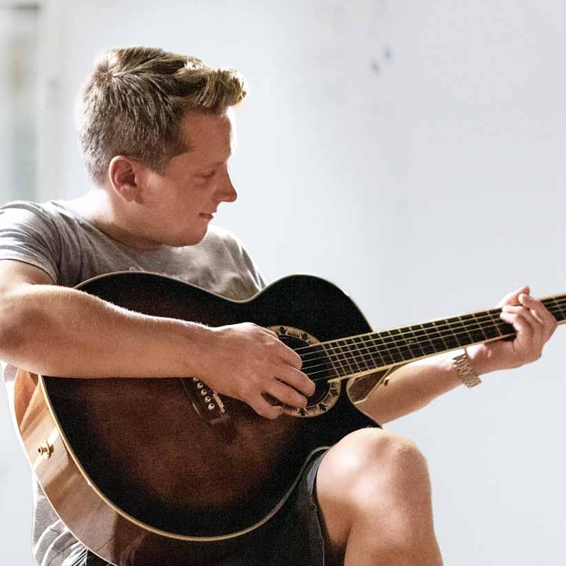 Lächelnder Mann in Shorts und T-Shirt spielt Gitarre – Carsten Ahlf