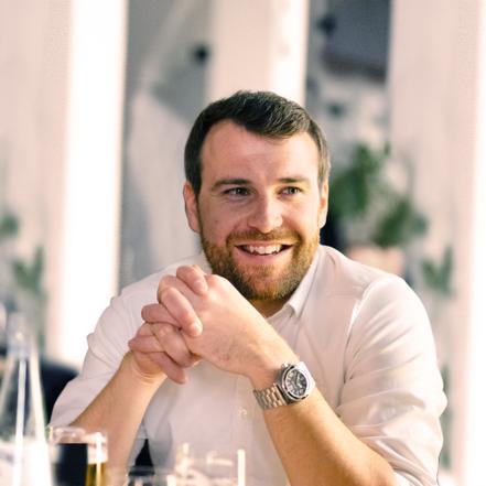 lächelnder junger Mann (Max Mümken) im weißen Hemd im Restaurant