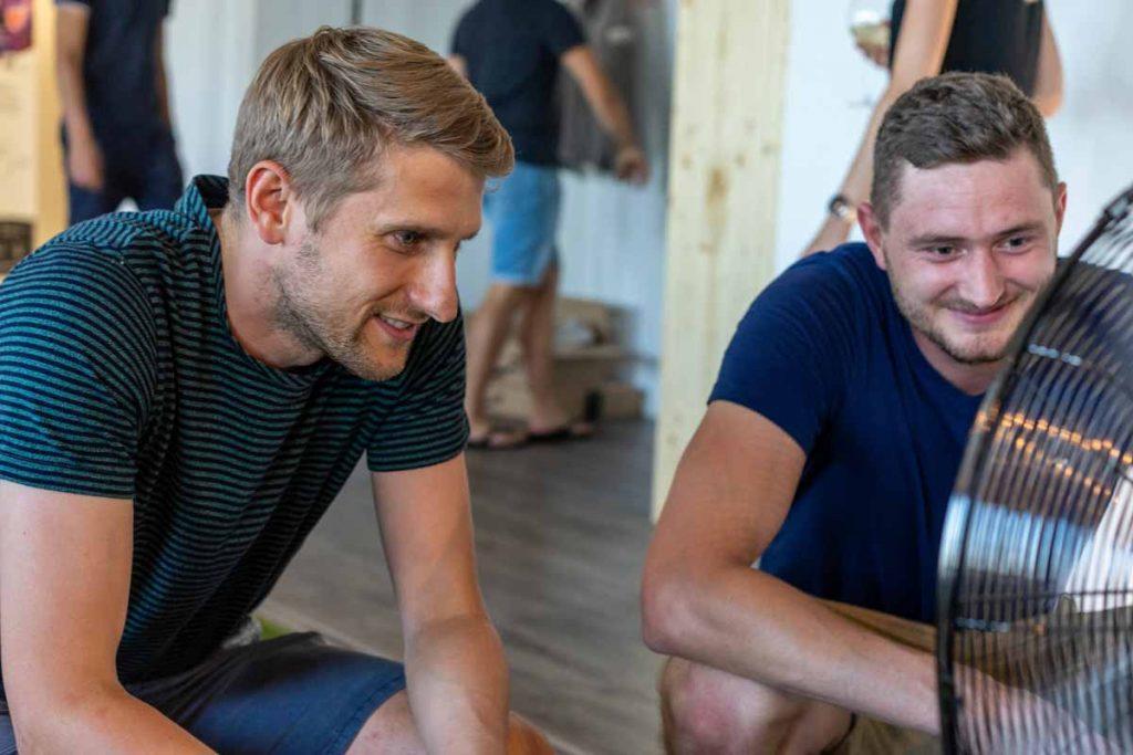 Zwei junge Männer – Tristan und Mario – kühlen sich vor einem Ventilator ab