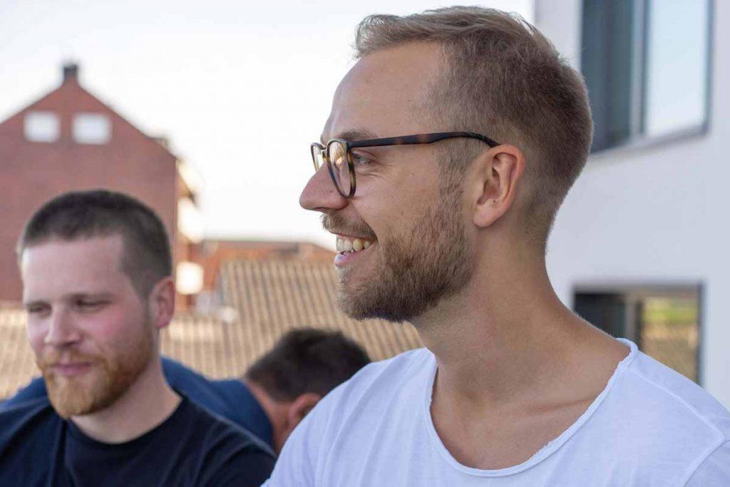Patrick Lukas lächelnd auf der Dachterasse