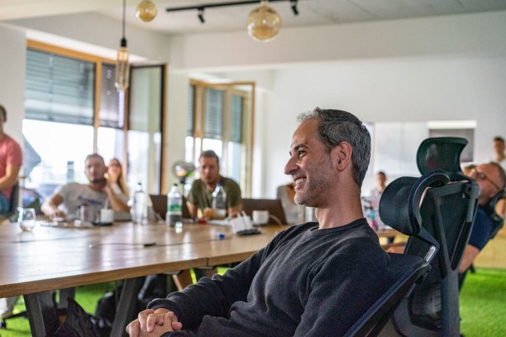 André Brühl hört lächelnd einem Vortrag zu