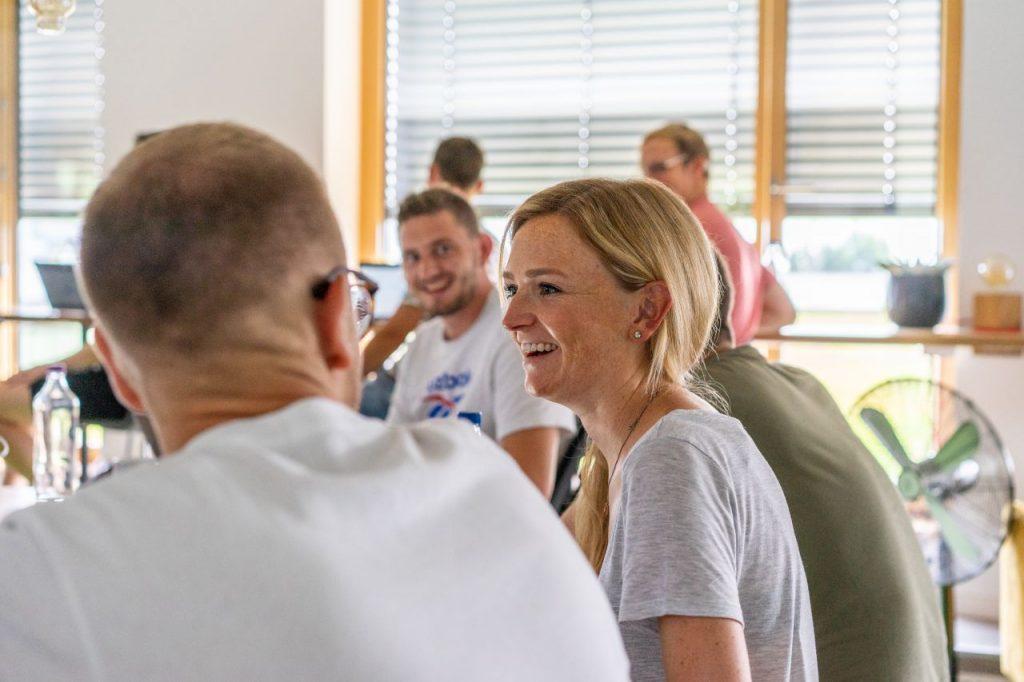 Svenja Krämer lacht zusammen mit ihren Kollegen in einem Meeting