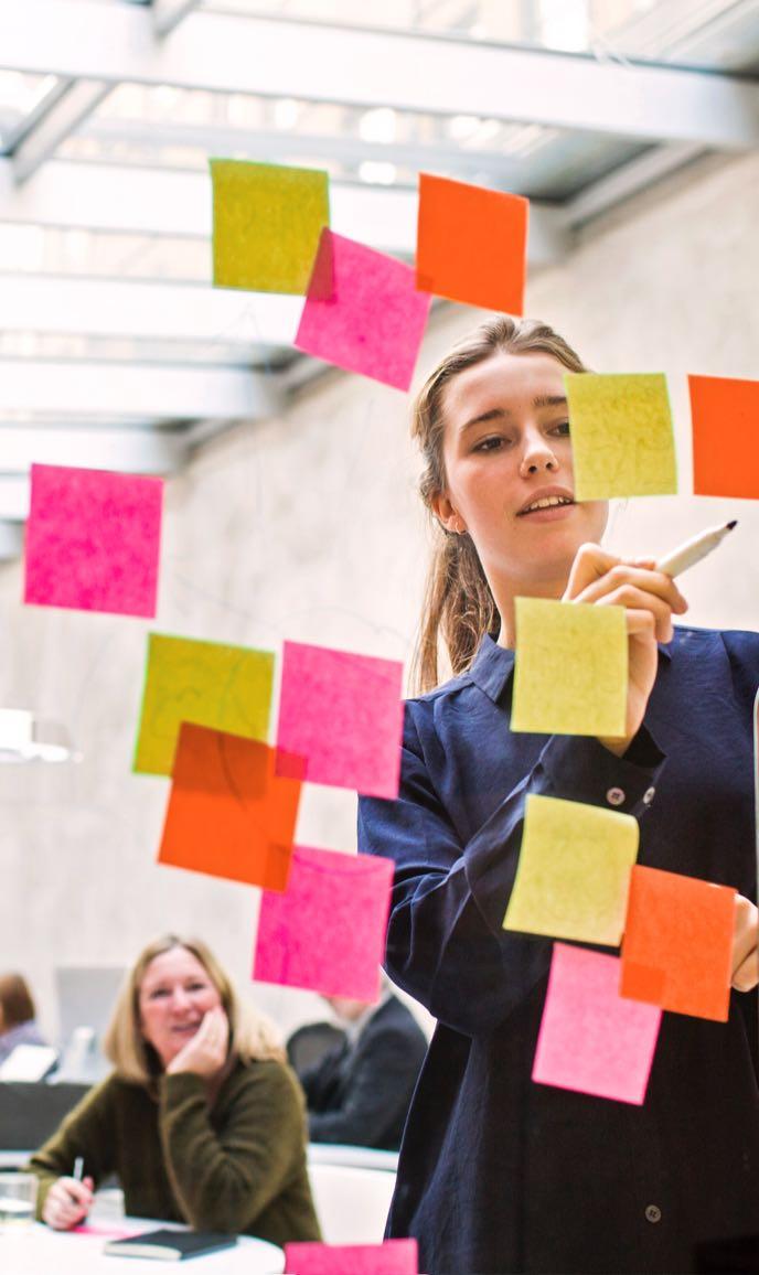 junge Business Frau erarbeitet mit Team Strategie auf Klebezetteln