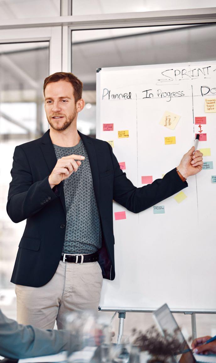 Junger Business-Mann erklärt Kunden etwas am Whiteboard