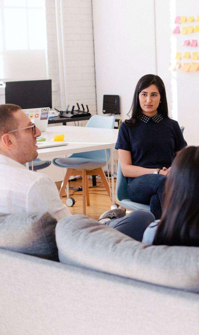 Frau hört aufmerksam zwei Kunden zu