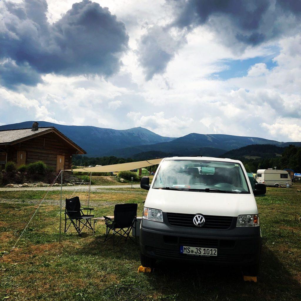 Kleintransporter mit Campingstühlen vor grüner Landschaft und Bergkette