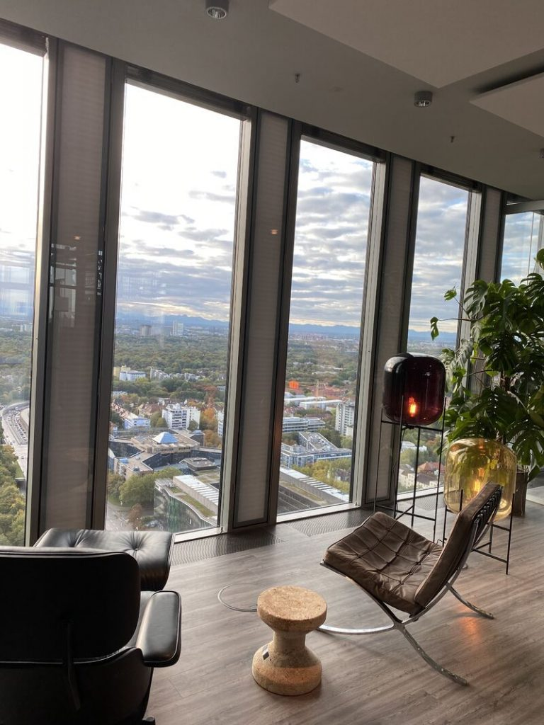 Wohnlich eingerichtetes Büro mit Blick über München und Berge